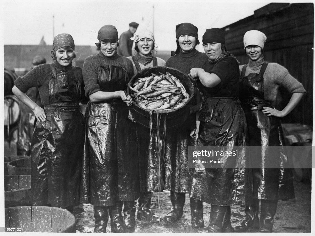 A view as Scotch fishing girls examine their herring catch at Yarmouth Scotland Circa 1900