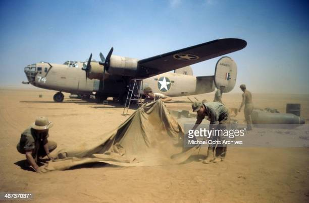 A view as the 376th Bombardment Group work in the blowing sand with a B24Liberator in the background at the US Air Force Base in Benghazi Libya