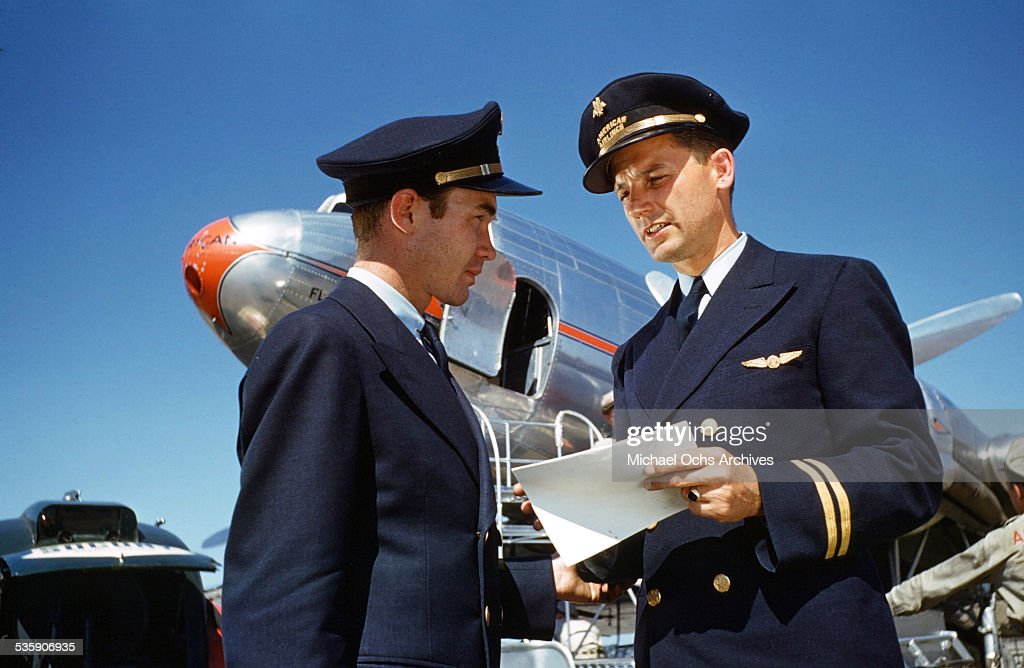 A view as the pilots talk on the runway as a Convair Liner sits behind them for American Airlines.