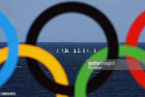 A view as the Sailing gets underway through the Olympic Rings from the Men's Preliminary Pool E Match 35 of the beach volleyball on Day 6 of the Rio...