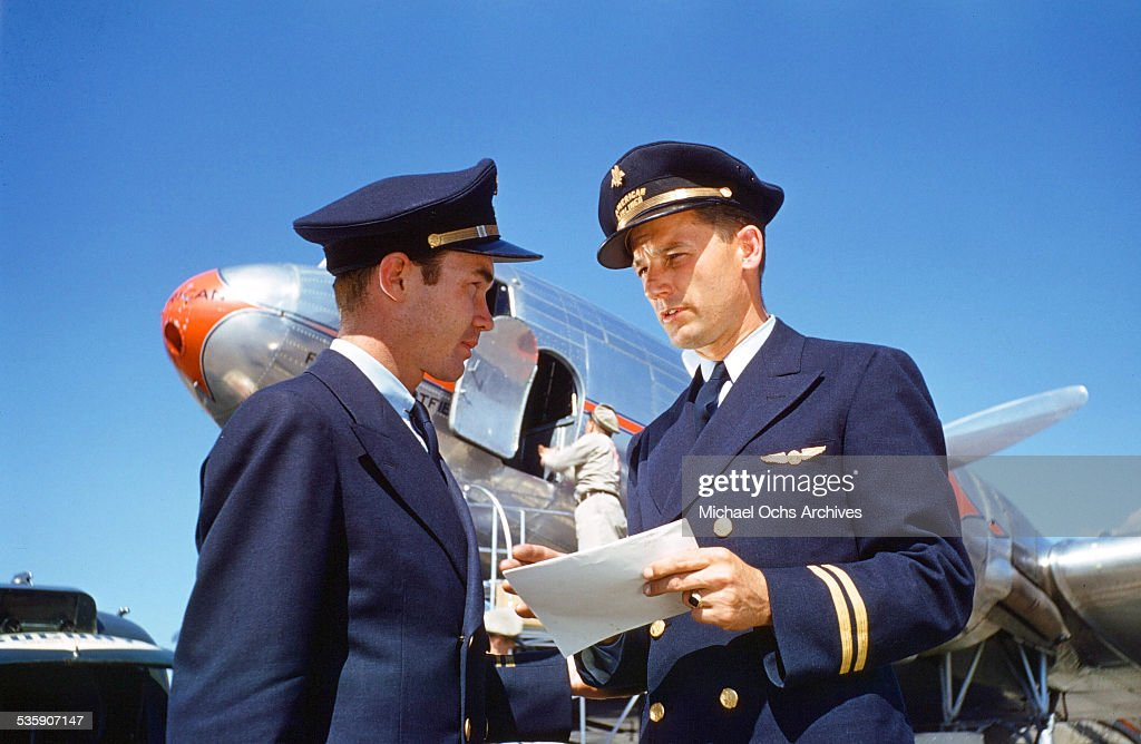 A view as two American Airlines pilots talk on the runway.