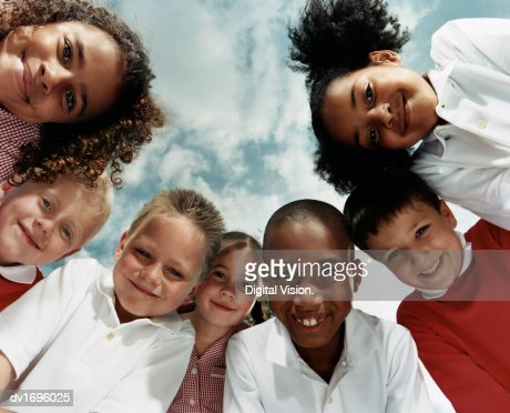 View Directly Below of Seven Primary School Children Huddled Together Looking at the Camera : Stock Photo