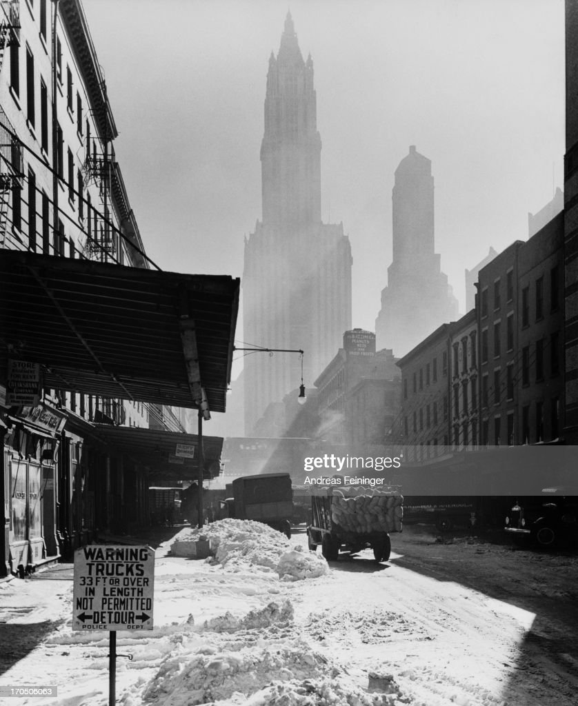 A view down a snowy street in New York City with the Woolworth Building and Transportation Building in the background 1940