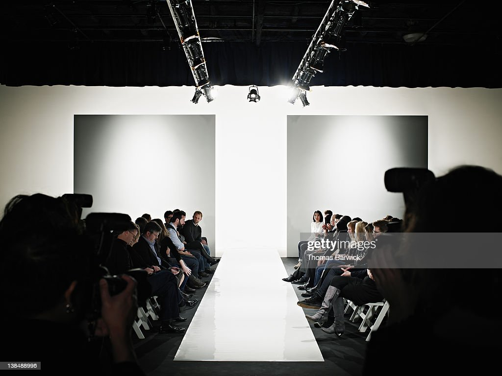 View down catwalk of photographers and crowd : Stock Photo