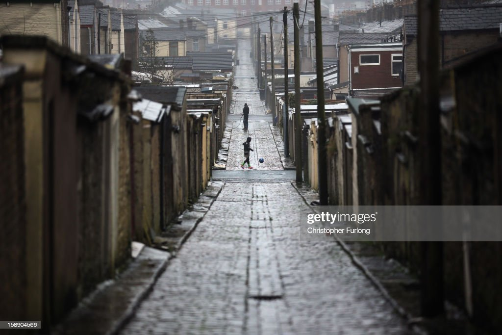 A view down the rear alleway at the back of homes in Accrington. Lancashire has the highest amount of empty homes in England on January 3, 2013 in Accrington, England. There are estimated to be 850,000 empty homes in the United Kingdom even though local councils still have long waiting lists for housing. The terraced houses were due to be rejuvenated by Accrington council but the project was put on hold when the government cut a housing regeneration project.