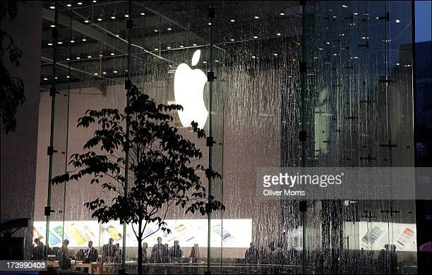 A view during a rainstorm of the illuminated Apple store designed by Bohlin Cywinski Jackson on Manhattan's Upper West Side New York June 13 2013
