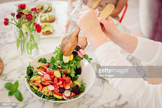 View from above of a table laid with cutlery and plates of prepared food. A woman taking a serving of salad.
