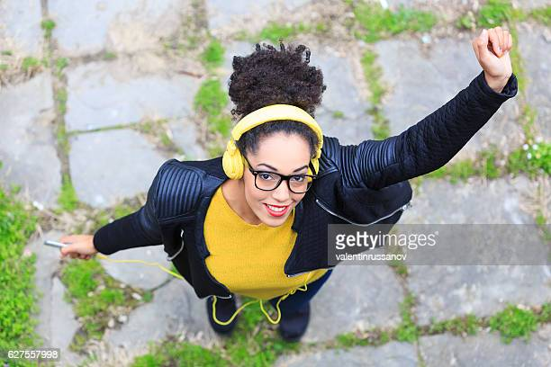 View from above of attractive young woman with yellow headphones
