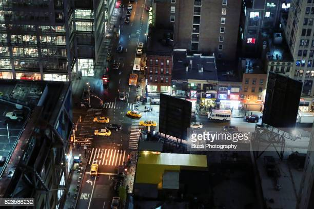 View from above of busy intersections and rooftops in Midtown Manhattan at night, New York City