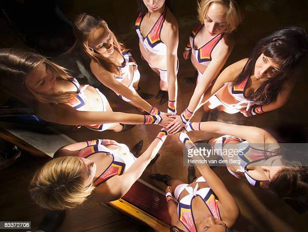 View from above of cheerleaders with their hands in middle of circle,