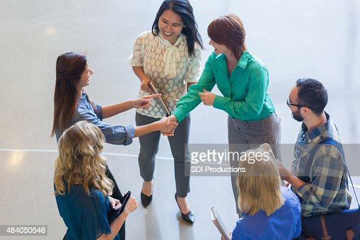 View from above of creative business team shaking hands