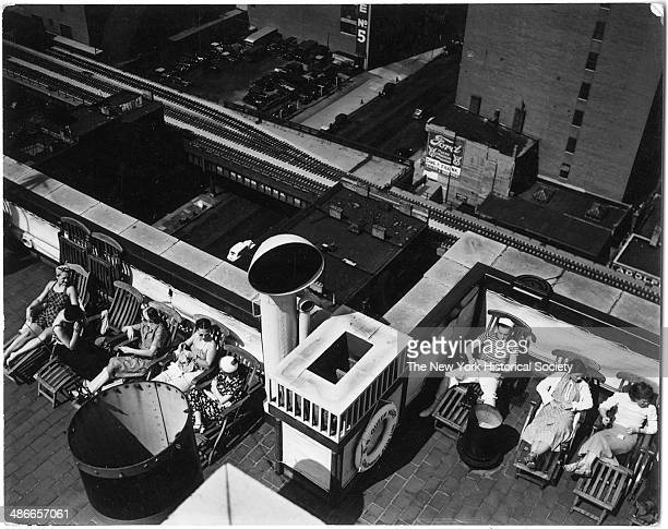 View from above of people relaxing in lounge chairs on the ship deck roof atop the London Terrace looking over the high line on 23rd Street New York...
