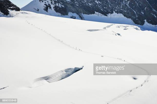 View from above of people walking on the Jungfrau-Aletsch Glacier Switzerland