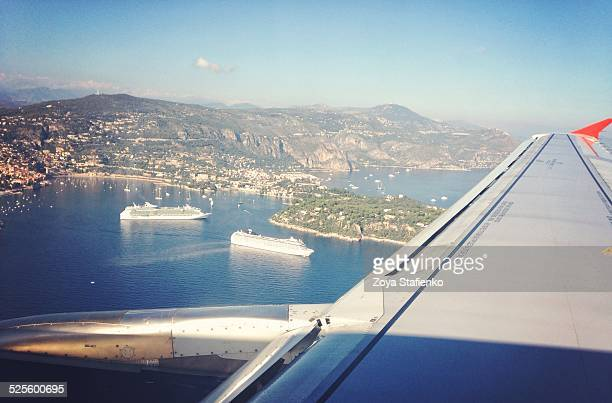 View from airplane window of coastline sea and cruise ships behind engine and wing