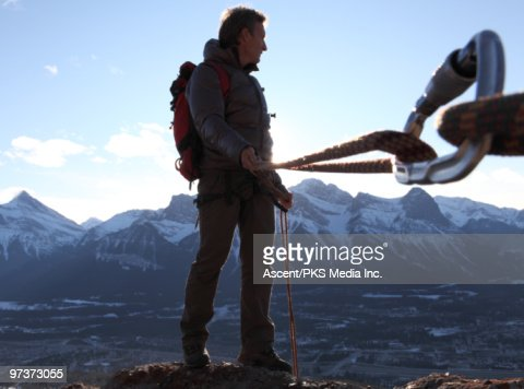 View from anchor of mountaineer stepping off cliff