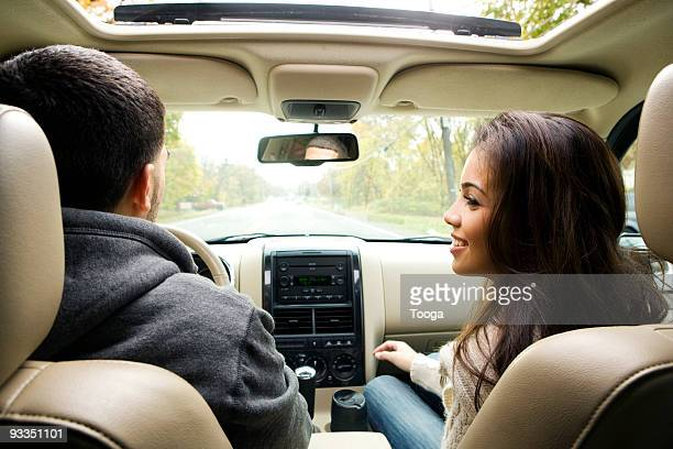 View from backseat of young couple in car