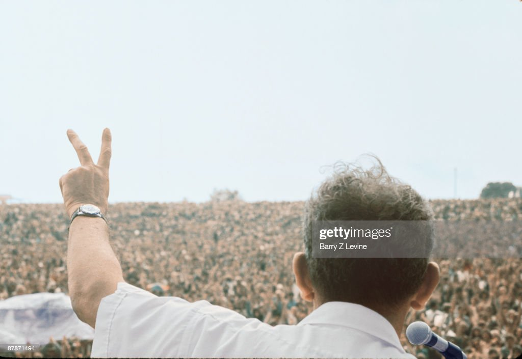 View from behind American farmer Max Yasgur (1919 - 1973) as he addresses the massive crowd with a 'peace sign' from stage during the Woodstock Music and Arts Fair in Bethel, New York, August 17, 1969. Yasgur provided the land, part of his farm, upon which the festival was held after several other locations had fallen through.