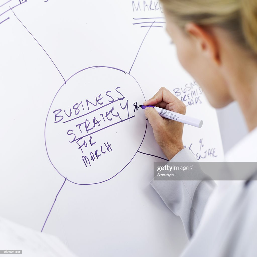 view from behind of a businesswoman writing on a presentation diagram : Stock Photo