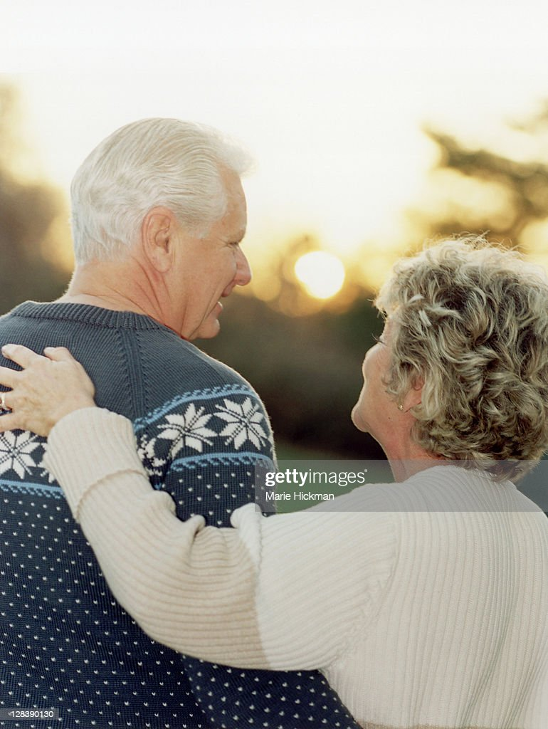 View from behind of a man, 64 years old, and woman 60 years old at sunset : Stock Photo