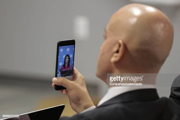 View from behind of a United Nations participant using a cellphone to videotape a speech by Nikki Haley United States Permanent Representative to the...