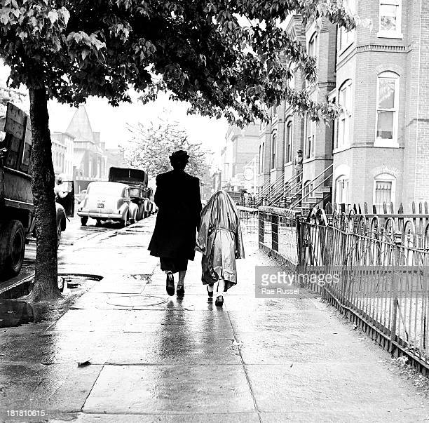 View from behind of a woman as she walks with her daughter along a rainy sidewalk Brookly New York New York 1948
