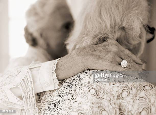 view from behind of an elderly woman arm on another woman's shoulder