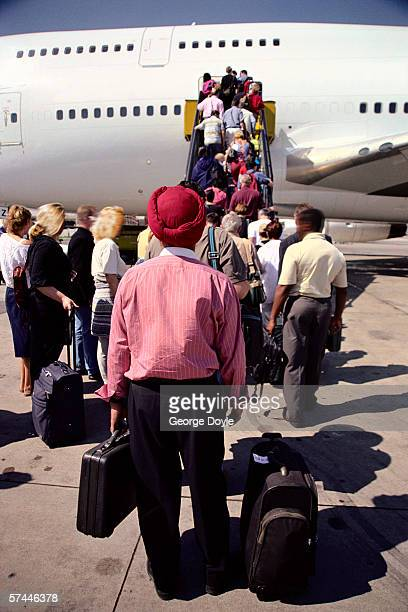 view from behind of passengers boarding an aircraft