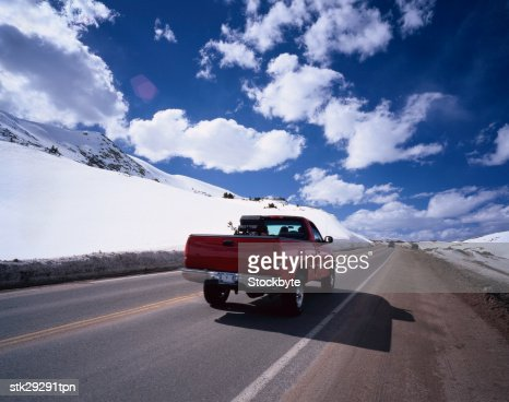 view from behind of pickup truck driving on a snow lined street