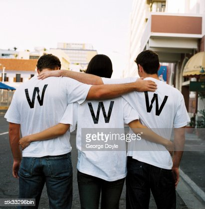 view from behind of three men wearing www on their t-shirts : Stock Photo