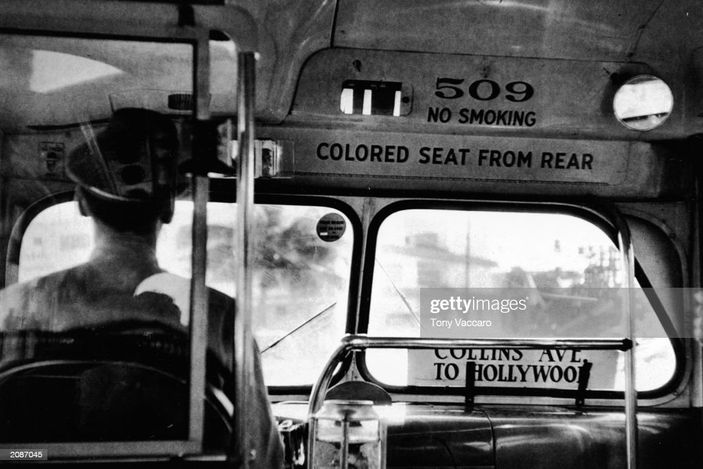 View from behind the back of a bus driver with a sign on the front of the vehicle that reads 'colored seat from rear' California circa 1955