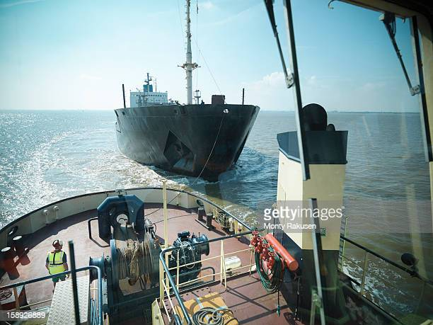 View from bridge of tugboat of ship being towed at sea
