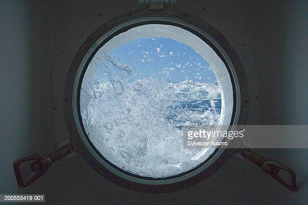 View from cabin porthole with water splashing on it