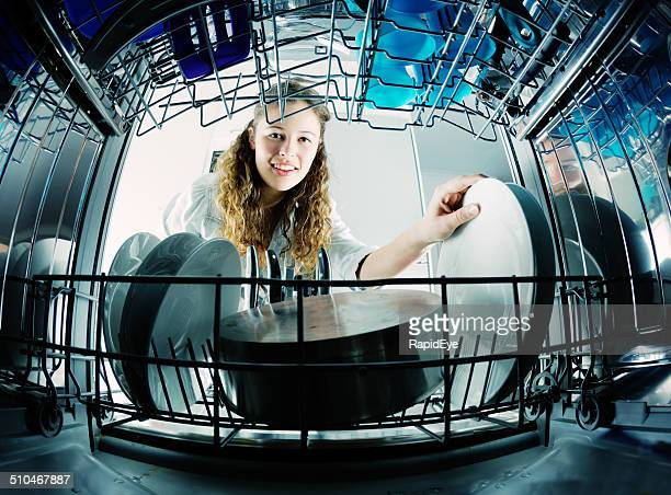 View from inside dishwasher of pretty young woman loading dishes