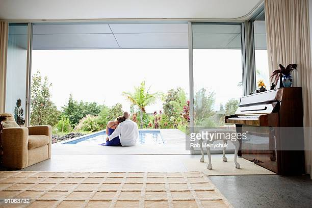 View from Living room to couple seated by pool.