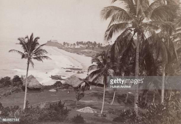 A view from Mount Helicon across a beach to the Santo Antonio da Barra Lighthouse Salvador Bahia Brazil circa 1860