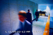 Businessmen walking in a corridor viewed from a surveillance camera