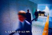 Businessmen walking in a corridor viewed from a surveillance camera