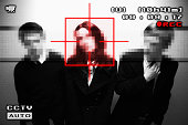 Pixelated portrait of people viewed from a surveillance camera, woman being marked with red square