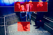 Business people in an elevator viewed from a surveillance camera, being marked with red squares