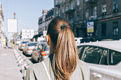 View from the back of a girl with brown hair walking through the city in summer