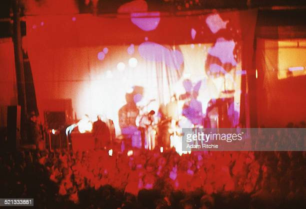 A view from the back of the venue showing the crowd at the Roundhouse watching Pink Floyd perform in front of a psychedelic light show projection...