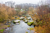View from the bridge on a small river that flows through the boulders and the granite stone  canyon in the background on the hillside park with pavilions and stairways. Autumn and rainy weather