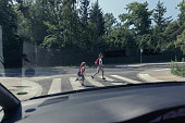 View from the car on children running on pedestrian crossing