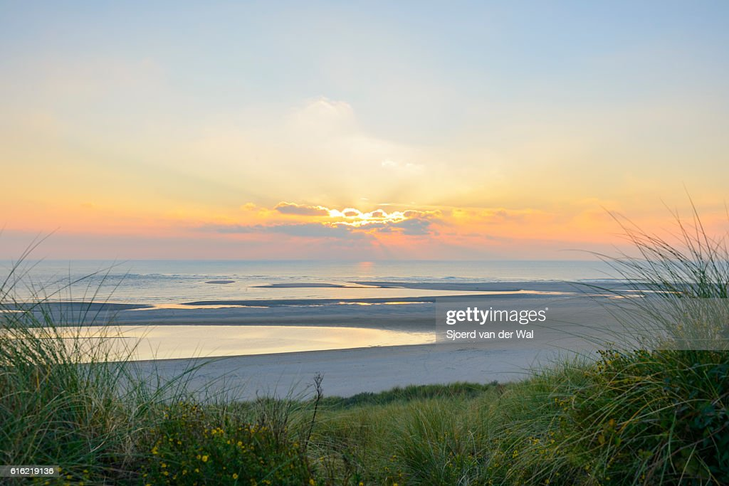 View from the dunes of a sunset at the beach : Bildbanksbilder