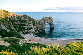View from the hill over people walking on a beach by the sea and Durdle Door, a natural limestone arch on Dorset's Jurassic Coastline, UK
