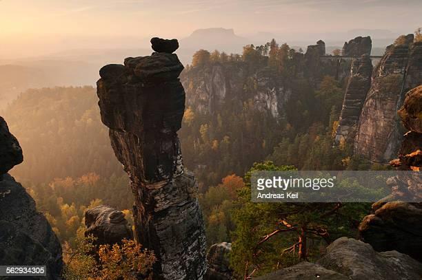 View from the Hoellenhundaussicht view over the Wehlgrund valley to the Bastei rock formation and Basteibruecke bridge, dawn, sunrise, autumn, Saxon Switzerland, Saxony, Germany, Europe