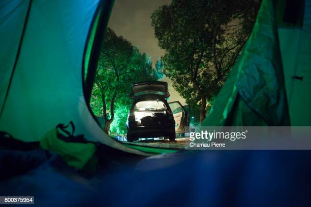 View from the inside of the tent, Car open and lit in the middle of the night, night shoot
