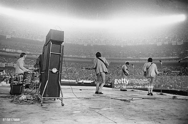 A view from the side of the stage showing fans in the crowd as The Beatles perform at Shea Stadium New York August 23 1966 LR Ringo Starr George...