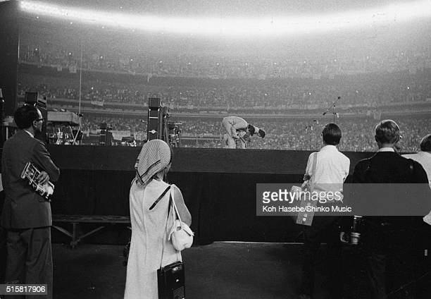 A view from the side of the stage showing The Beatles taking a bow at the end of their show and the crowds behind at Shea Stadium New York August 23...