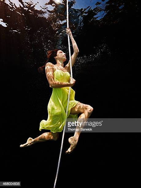 View from underwater of woman climbing up rope
